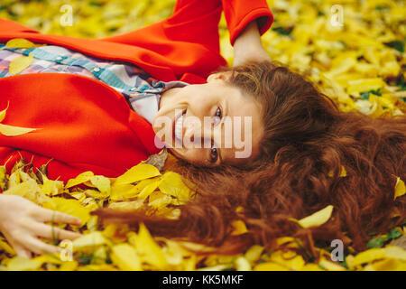 Junge hübsche Dame umgeben Blätter im Herbst