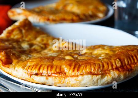 Hintergrund der zwei großen Empanadas (Fleisch, Chicken Pie) auf einem Teller. Freiheitsgrad - Stockfoto