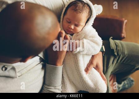 Blick von oben auf die kleine Baby schlafend in den Armen seines Vaters. Neugeborenen Sohn mit Vater sitzt auf einem - Stockfoto