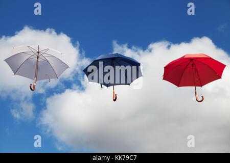 Drei schwimmenden Sonnenschirme in Weiß, Blau und Rot - Stockfoto