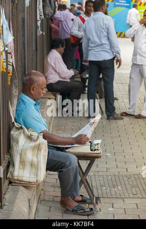 Rechtliches Dokument Schreibkraft lesen Zeitung in der Straße vor Bombay High Court in Mumbai, Indien - Stockfoto