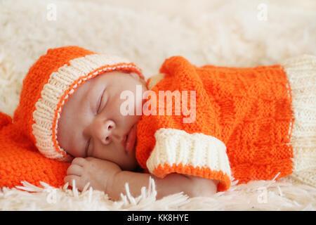 Süß schlafen neugeborene Baby in einen gestrickten orange Kostüm auf weiße Decke gekleidet. - Stockfoto