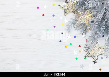 Christmas tree branch mit Girlande Lampen geschmückt, auf weißem Hintergrund aus Holz mit bunten Konfetti - Stockfoto