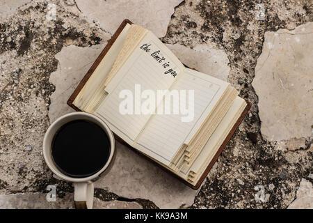 Die Grenze ist sie ein Angebot für ein Notebook und eine Kaffeetasse in der Nähe von Es Stein - Stockfoto