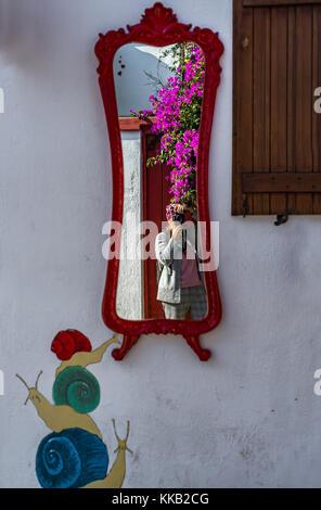 Die Fotografin Reflexion in alte rot gerahmten Spiegel - Stockfoto