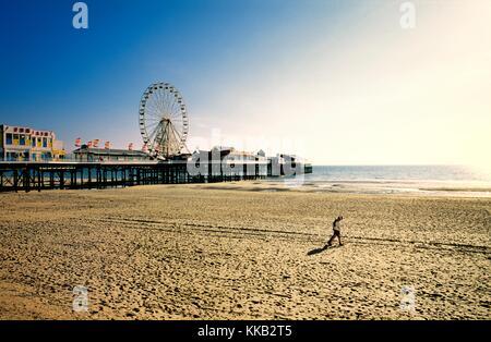 Paar am Strand von Blackpool mit Pier Riesenrad Kirmes. Liebhaber entlang Sandstrand. Lancashire, England. Sommerabend. - Stockfoto