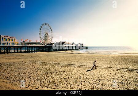 Paar am Strand von Blackpool mit Pier Riesenrad Kirmes. Liebhaber, sandigen Strand entlang spazieren. Lancashire, - Stockfoto