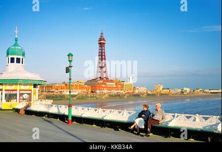 Ältere Paare sitzen auf North Pier in Blackpool Beach mit Blackpool Tower hinter. Lancashire, England, UK. Sommer. - Stockfoto