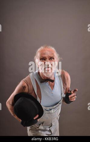 Alte mocking Bettler und hielt seinen schwarzen Melone und seine Zunge angezeigt - Stockfoto