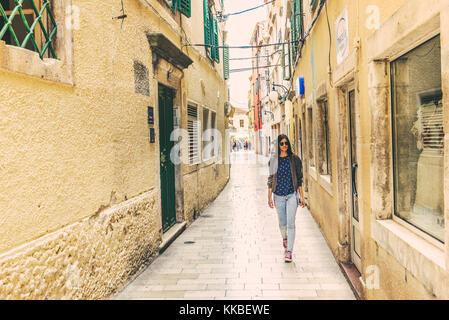 Nicht identifizierte Mädchen zu Fuß auf der Straße von Sibenik, ein beliebtes Reiseziel für historische Architektur, - Stockfoto