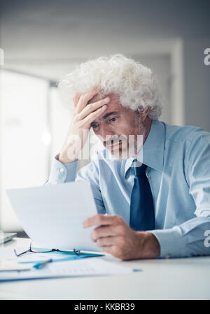 Schockiert Geschäftsmann empfängt fehlerhafte Nachrichten verwirrt, lesen einen Brief und berührt seine Stirn, Ausfall - Stockfoto