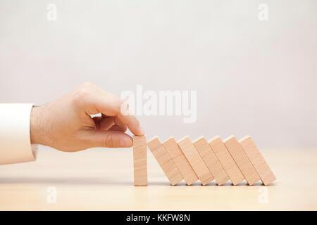 Des Menschen Hand anhalten der Domino Effekt. Konzept Bild für Unternehmensstrategie und Krise Lösung. - Stockfoto