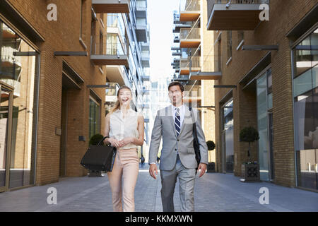 Geschäftsmann und Geschäftsfrau zu Fuß zur Arbeit durch die Stadt. - Stockfoto