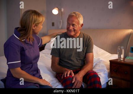 Krankenschwester im Gespräch mit älteren Mann im Schlafzimmer zu Hause besuchen - Stockfoto