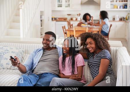 Vater sitzt auf einem Sofa Fernsehen mit Töchtern im Teenageralter - Stockfoto