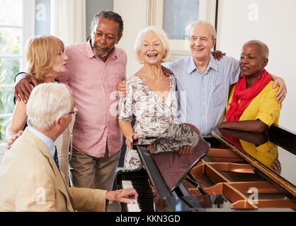 Gruppe von Senioren stehen von Piano und Gesang - Stockfoto
