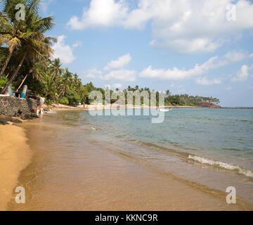 Tropischen Sandstrand und Kokospalmen um eine geschwungene Bucht, Mirissa, Sri Lanka - Stockfoto