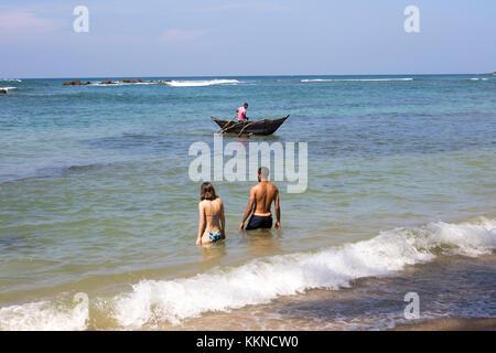 Touristen Baden im Meer Mann angeln mit traditionellen Outrigger Kanus, Mirissa, Sri Lanka, Asien - Stockfoto