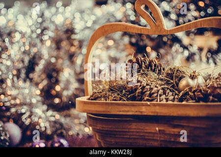 Bunte goldene Weihnachtsschmuck aus Holz Korb mit Tannenzapfen mit entsättigt Verstärkungseffekt gemacht. Extrem - Stockfoto