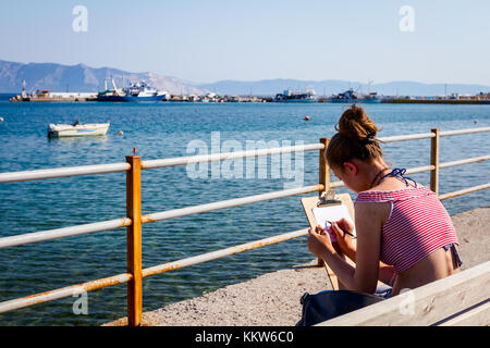 Junge Mädchen Künstler ist ausgehend von ihren Vorstand, angedockt Fischerboote auf lokaler Port verankert. - Stockfoto