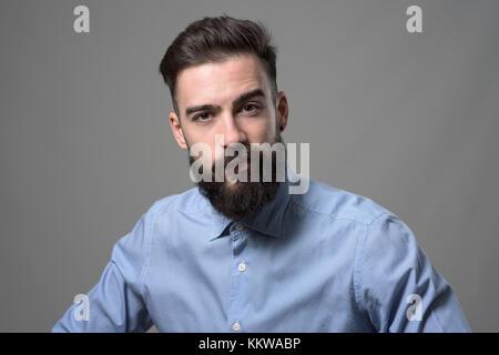 Skeptisch verdächtige junge Bartgeier stilvolle Geschäftsmann an Kamera suchen mit hochgezogener Augenbraue gegen - Stockfoto