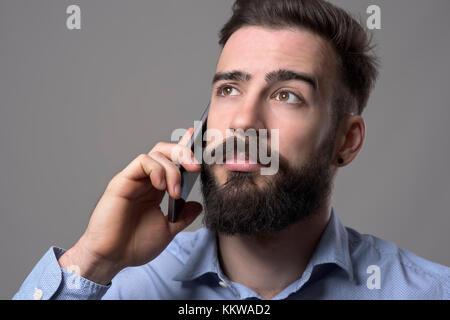 Nahaufnahme Portrait von junge Bartgeier business Mann auf dem Mobiltelefon an Copyspace gegen Grau studio Hintergrund - Stockfoto