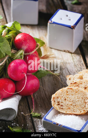 Frisches nass Radieschen mit Salz und Brot über alten Holztisch. siehe Serie - Stockfoto