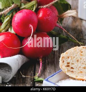 Frisches nass Radieschen mit Salz und Brot über alten Holztisch. square Bild mit selektiven Fokus - Stockfoto