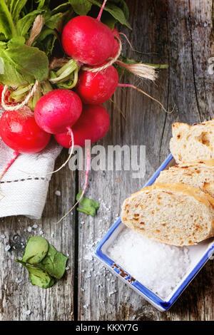 Frisches nass Radieschen mit Salz und Brot über alten Holztisch. top View - Stockfoto