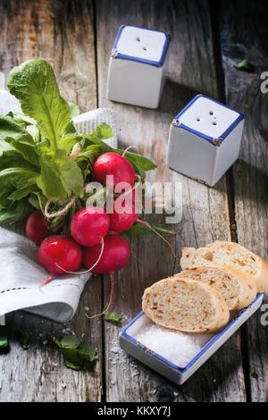 Frisches nass Radieschen mit Salz und Brot über alten Holztisch. - Stockfoto