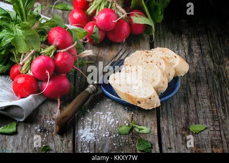 Frisches nass Radieschen mit Vintage Gabel, Salz und Brot über alten Holztisch. siehe Serie - Stockfoto
