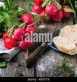 Frisches nass Radieschen mit Vintage Gabel, Salz und Brot über alten Holztisch. square Bild - Stockfoto