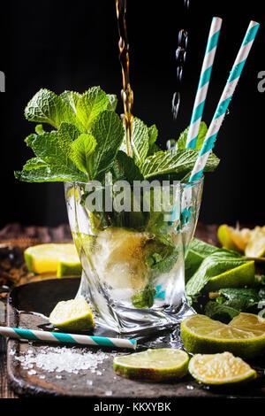 Glas mojito Cocktail mit Gießen rum und Soda, frischer Minze, Limonen und Eiswürfel über schwarzen Hintergrund. - Stockfoto