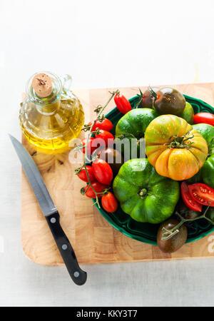 Zutaten für Salat aus verschiedenen Arten von Tomaten auf einem weißen Tisch aus Stein. Schneidbrett, Olivenöl und - Stockfoto