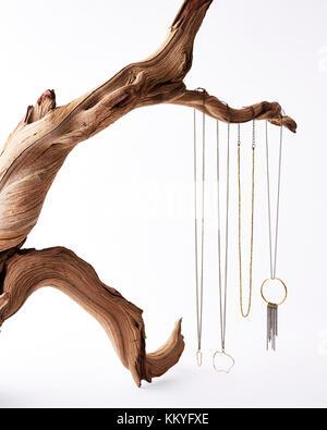 Filigrane Handarbeit Gold und Silber Halsketten hängen von einem verdrehten Treibholz Zweig auf weißem Hintergrund - Stockfoto