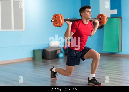 Junger Mann Training mit Fitness Bar in der Turnhalle mit Tageslicht - Stockfoto