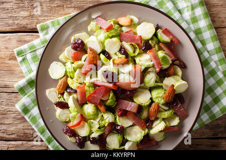 Hausgemachten Salat von Scheiben Rosenkohl, Preiselbeeren, Mandeln und Schinken close-up auf einem Teller auf dem - Stockfoto