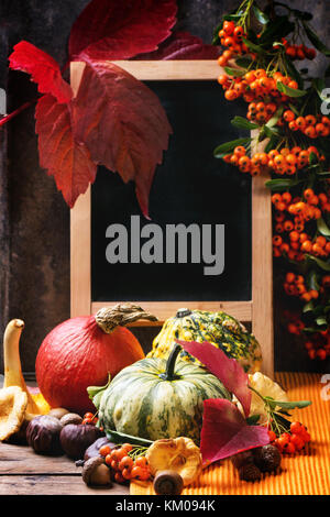 Kürbisse, Nüsse, Beeren und Pilze Pfifferlinge mit leeren Tafel über alten Holztisch. siehe Serie - Stockfoto