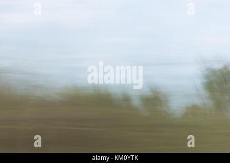Verschwommenen Landschaft aus einem fahrenden Fahrzeug mit hohen grünen Gras im Vordergrund und leichte blaue Himmel - Stockfoto