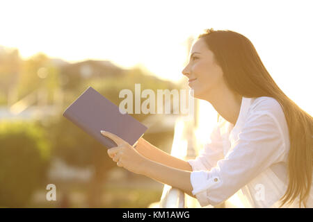 Seitenansicht Porträt einer Frau träumen, lesen Sie ein Buch aus Papier im Freien an einem Balkon bei Sonnenuntergang - Stockfoto
