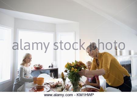 Großmutter und Enkelinnen dekorieren, Einstellung der Tabelle für Thanksgiving Abendessen - Stockfoto