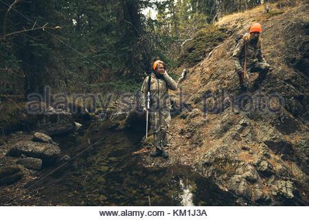 Mutter und Tochter Jäger mit Jagdwaffen absteigend Rock im Wald - Stockfoto