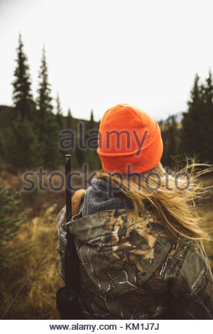 Frau Jäger in der Tarnung und orange Mütze tragen Jagdgewehr im Feld - Stockfoto