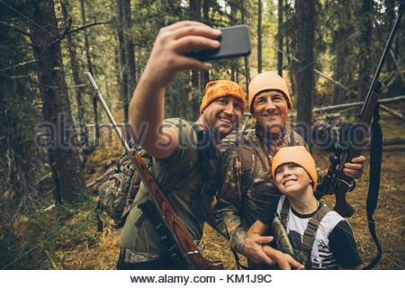 Multi-Generation männlichen Jäger mit Jagdwaffen unter selfie mit Kamera Handy im Wald - Stockfoto