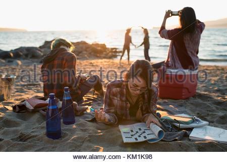 Bruder und Schwestern entspannend, Fotografieren mit der Kamera Handy und Kreuzworträtsel am sonnigen Strand - Stockfoto