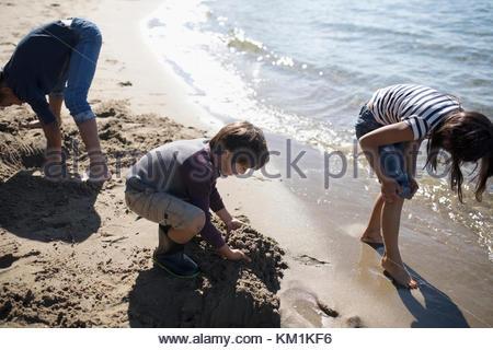 Junge und Mädchen Freunde spielen, Graben im Sand an sonnigen Strand - Stockfoto