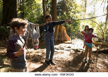 Junge und Mädchen Freunde mit Stöcken spielen in Sunny woods - Stockfoto