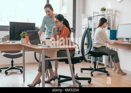 Gruppe von Design Team erzielen die besten Ergebnisse. Zwei selbstbewussten jungen Frauen auf der Suche nach laptop - Stockfoto