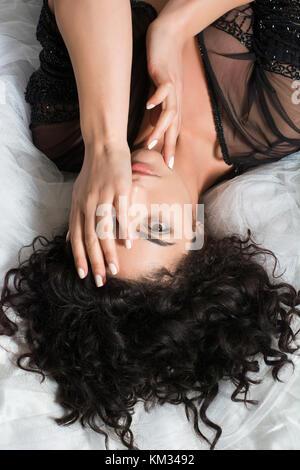 Ernsthafte junge Frau zur Festlegung im Bett Hand, Auge - Stockfoto