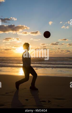 Volle Länge, Silhouette eines kleinen Jungen spielen mit dem Ball am Strand bei Sonnenuntergang - Stockfoto